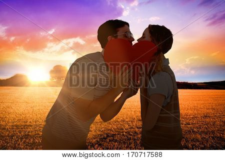 Geeky hipster couple kissing behind heart card against countryside scene