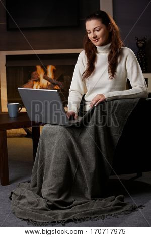 Young woman sitting at home at fireplace, covered in blanket, using laptop computer, looking down, smiling.