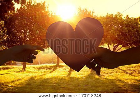 Couple passing a paper heart against sunrise over trees