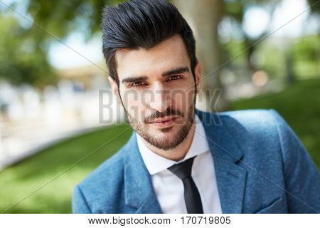 Outdoor closeup portrait of handsome young businessman looking at camera.