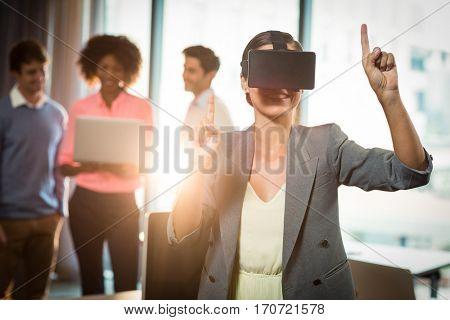 Businesswoman wearing virtual glasses in office