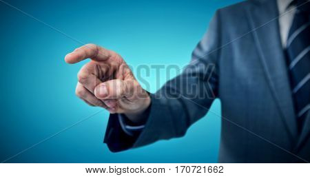Midsection of businessman pointing against blue vignette background