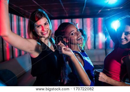 Smiling friends dancing on dance floor