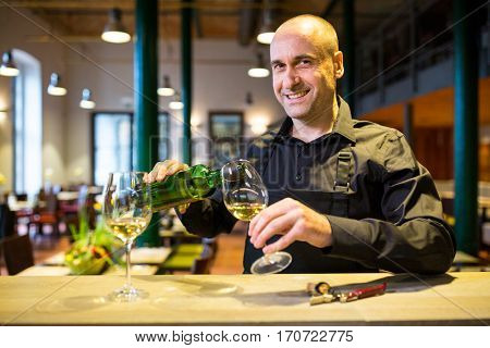 Portrait of waiter pouring white wine into glass in restaurant