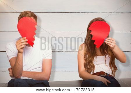 Couple holding broken heart against painted blue wooden planks