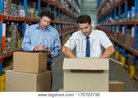 Managers are checking some cardboard boxes in a warehouse