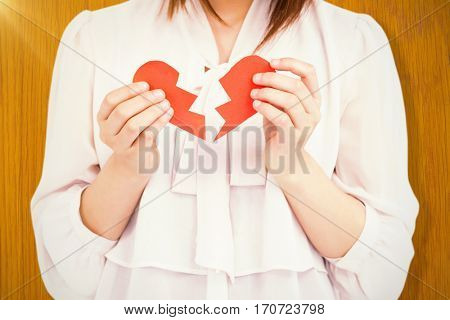 Woman holding broken heart paper against wooden pine table