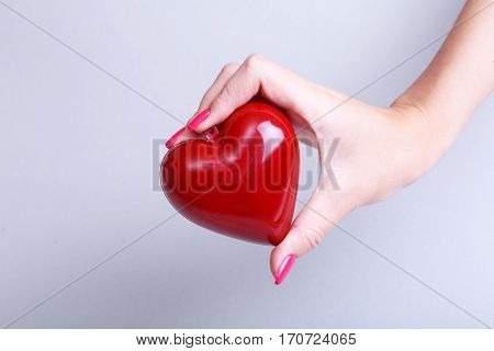 Female medicine doctor hold in hands red toy heart. Cardio therapeutist, student education, physician make cardiac physical, rate measure, arrhythmia concept.