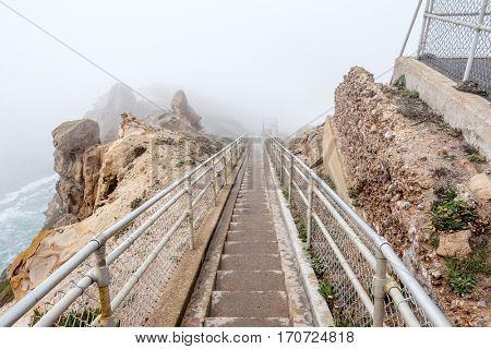 Trail through white fog to Point Reyes Lighthouse at Pacific coast, California, USA