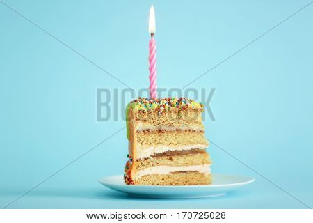 Slice of birthday cake with candle on color background