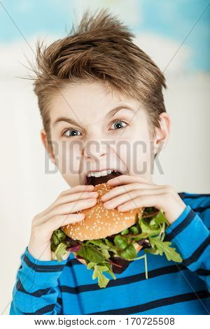 Young Boy Biting Into A Salad Burger
