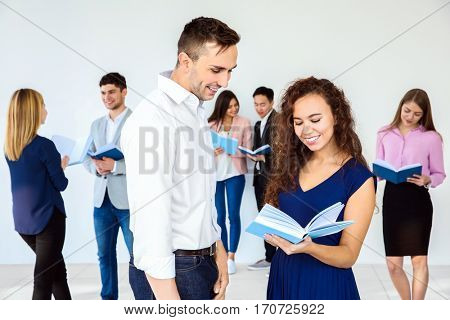 Young man and woman discussing book in club