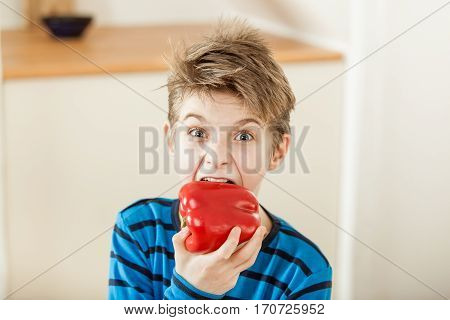 Surprised Young Boy Biting Into A Red Bell Pepper