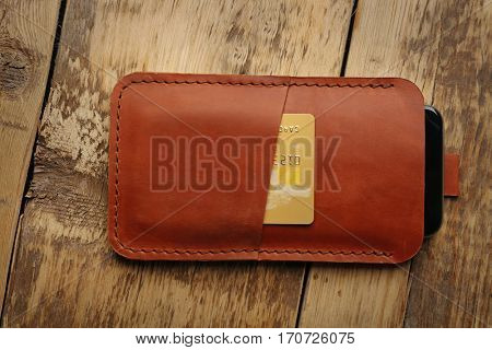 Leather case with mobile phone and credit card on wooden background