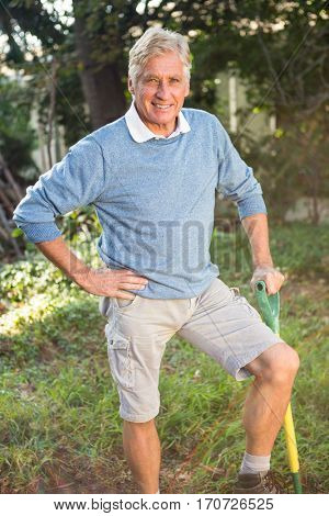 Portrait of happy mature male gardener with tool standing at garden