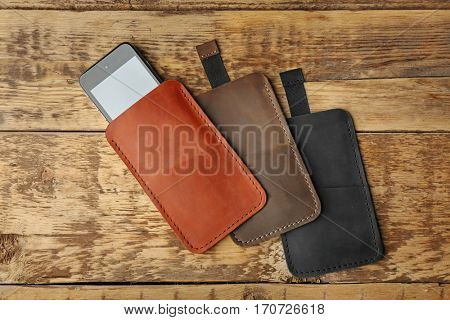 Leather cases for mobile phone on wooden background