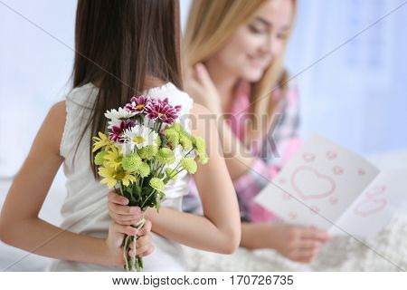 Cute little girl hiding flowers for her mother behind back, close up. Mother's day concept