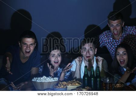 Young fans watching sports on TV late in evening with beer and snacks