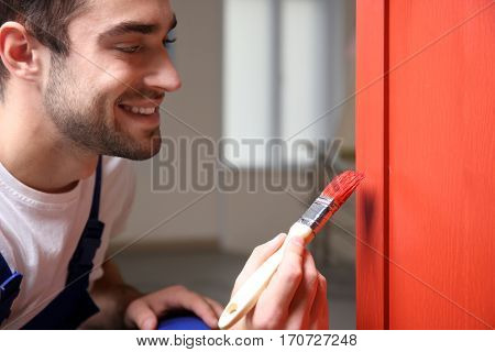 Close up view of young decorator painting furniture