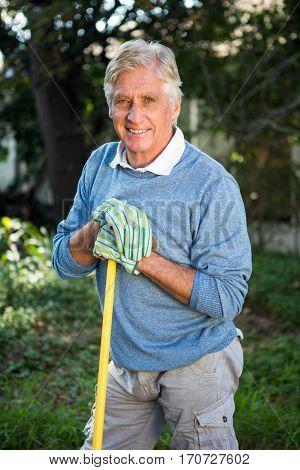 Portrait of happy mature gardener standing with tool at garden
