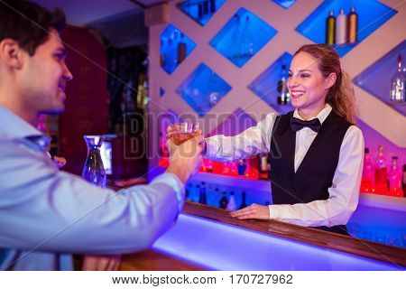 Young barmaid smiling while serving drink to male costumer at counter