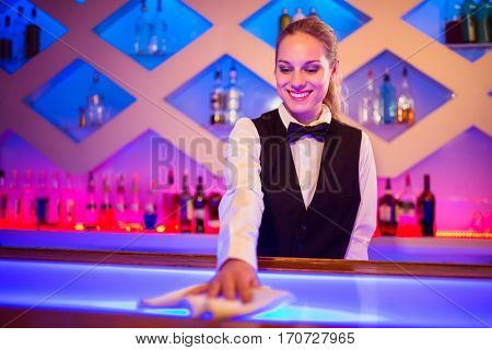 Barmaid smiling while cleaning illuminated bar counter