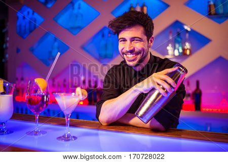 Portrait of bartender smiling while holding cocktail shaker at illuminated bar counter