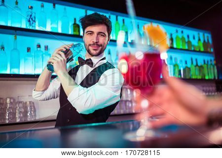 Portrait of confident handsome barkeeper preparing cocktail at bar counter
