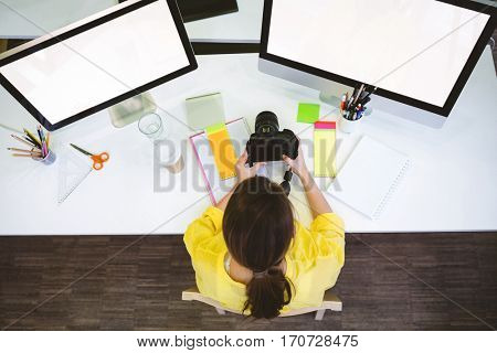 Overhead view of young female professional sitting with camera at desk in creative office