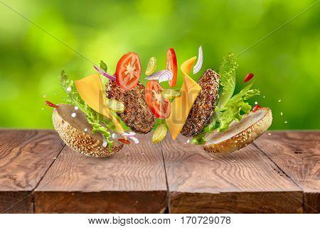 Hamburger ingredients against green background