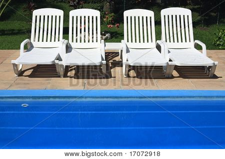 four white deckchair by the blue swimming pool