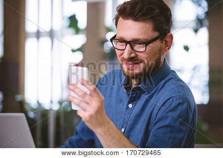 Happy young male executive using mobile phone at office