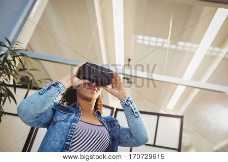 Low angle view of young businesswoman enjoying virtual reality headset at office