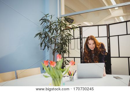 Confident young female executive using laptop in meeting room at creative office