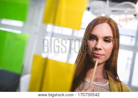 Businesswoman thinking while looking at sticky notes on glass