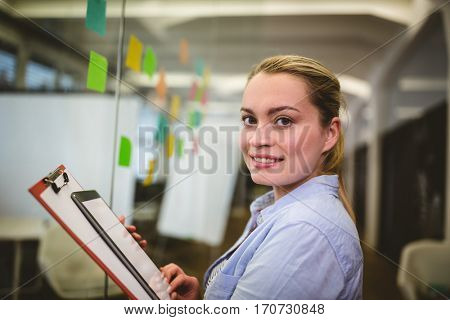 Portrait of smiling businesswoman holding note pad and digital tablet in creative office