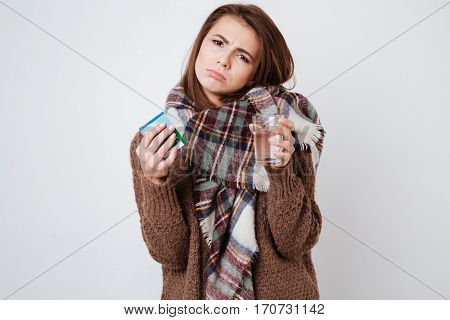Woman in sweater and scarf holding cup of water and medicament in hands and looking at camera. Isolated gray background