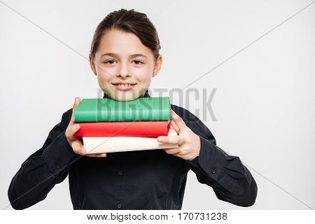 Picture of attractive young girl holding books isolated over white background.