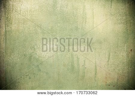 Green spray painted grunge stained wall with rust spots