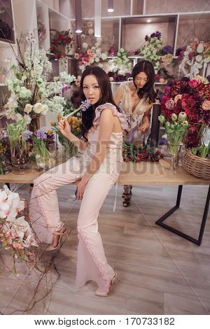 Fashion models in tender dresses posing and looking at camera. Beautiful asian florist girls with flowers in hands against floral background in flower shop indoors. Two attractive asian females florists working in store.