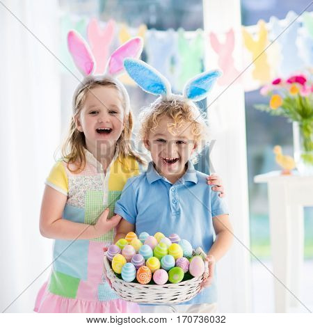 Little boy and girl in bunny ears holding a basket with colorful Easter eggs. Kids celebrating Easter. Children having fun on Easter egg hunt. Home decoration - pastel color bunny banner and flowers.