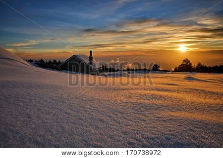 stone house in snow at sunset In Etna Park, Sicily