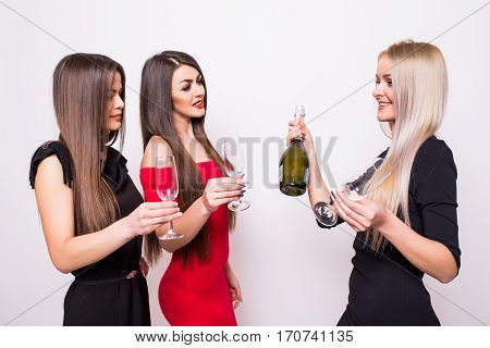 Three Smiling Young Women Celebrating And Drinking Champagne On The Party