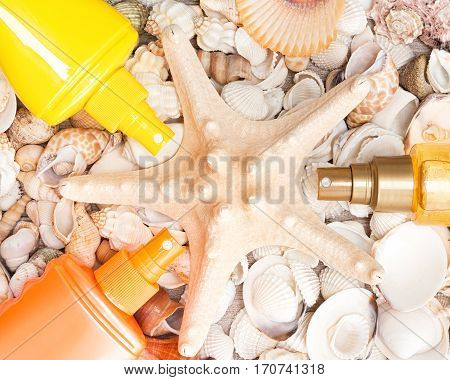 Starfish surrounded by containers of cosmetic sunscreen products with various shells. Concept of skin care cosmetics containing sun protection factor for beach vacation