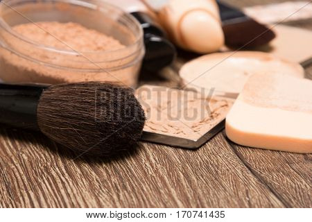 Foundation makeup products: liquid and cream foundation, powder with sponge and make up brushes. Shallow depth of field