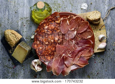 high-angle shot of a plate with an assortment of different spanish cold meats as chorizo, cured pork tenderloin and serrano ham, a piece of manchego cheese, bread and a cruet with olive oil on a table