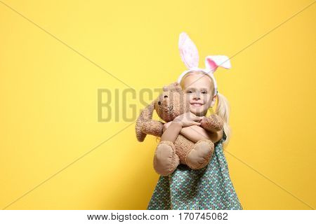 Cute little girl with bunny ears and cuddly toy on color background