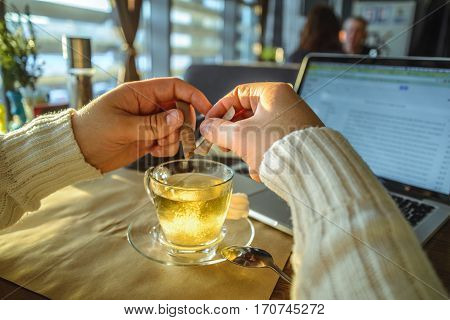 man in sweater working on laptop in caffe on sunset in front of window