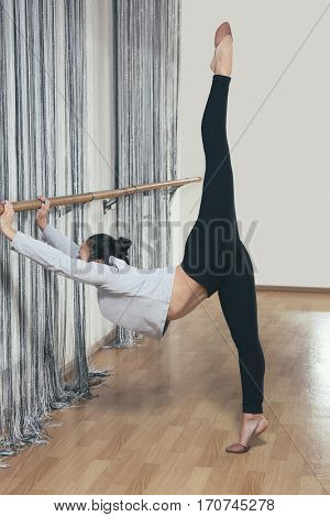 Young woman stretching near barre in dance studio