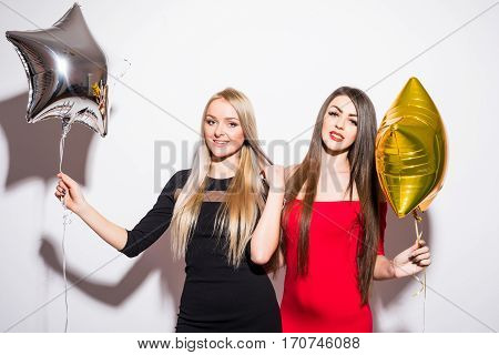 Two happy attractive yougn women having party over white background